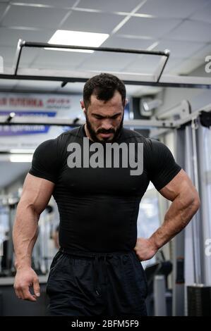 jeune homme barbu fort en jersey noir relaxant pendant l'entraînement de musculation dans la salle de sport Banque D'Images