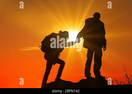 Aider les mains avec la lumière du soleil entre deux grimpeurs Banque D'Images