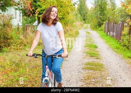 Young woman riding bicycle in summer city park à l'extérieur. Les personnes actives. Hipster girl vous détendre et rider moto. À vélo au travail au jour d'été. Location et de l'écologie concept de vie
