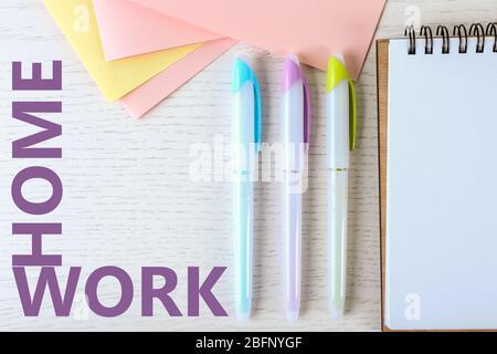 Composition de la couche plate des fournitures scolaires et des devoirs de mot sur fond en bois