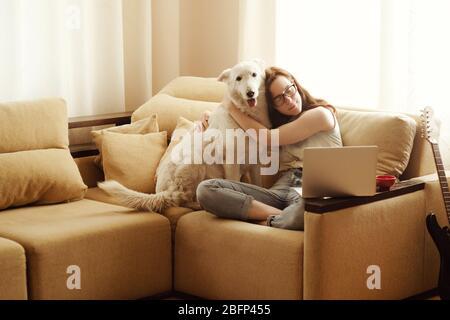 Belle femme assise sur un canapé et embrassant un chien.