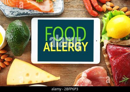 Concept de danger d'allergie. Tablette avec texte allergie alimentaire à l'écran. Différents aliments sur fond de bois.