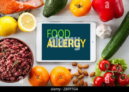 Concept de danger d'allergie. Tablette avec texte allergie alimentaire à l'écran. Différents plats sur fond blanc en bois.
