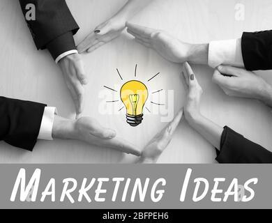 Concept d'idées marketing. Les gens d'affaires façonnent les mains en cercle autour du dessin d'ampoule sur fond de bois Banque D'Images