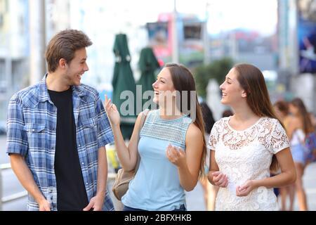 Un groupe heureux de trois amis riant et parlant dans la rue Banque D'Images