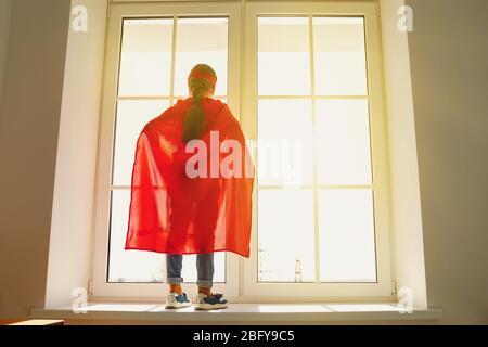 Fille enfant dans un costume de super-héros debout sur l'arrière-plan d'une fenêtre avec lumière du soleil regardant des rêves à la fenêtre