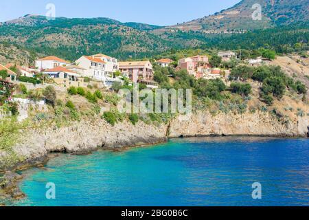 Vue sur une baie aux eaux turquoise et maisons traditionnelles colorées dans le village d'Assos, Kefalonia, Grèce Banque D'Images