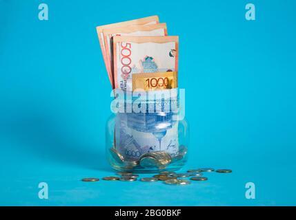 Tenge dans un pot en verre. Kazakhstan, KZ, KZT. Billets de banque, monnaie papier, pièces de monnaie, Banque. Salaire, crédit, épargne, salaire et dépenses. Affaires et économie.