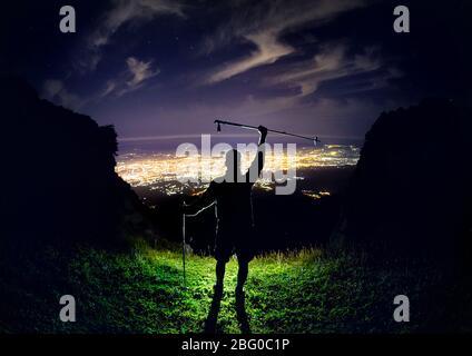 Homme avec pôle trekking au sommet du ciel nocturne avec des étoiles et éclatante lumière sous-ville Banque D'Images