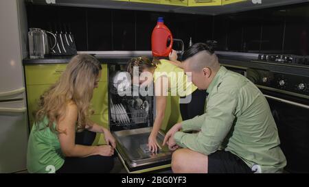 La mère et le père apprennent à utiliser le lave-vaisselle. Mistress fille enfants chargement mettre des plats sales dans le lave-vaisselle automatique. Banque D'Images