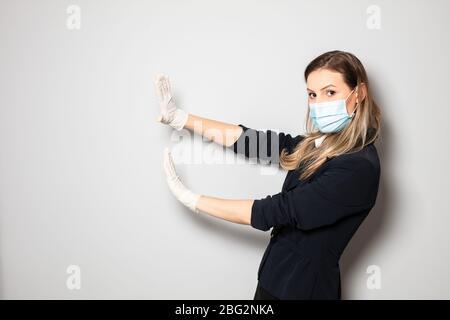 femme avec protection de masque et gants poussant quelque chose ou en mettant un arrêt de l'infection par le virus