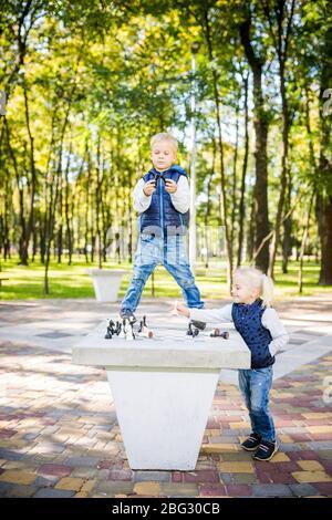 Passe-temps des enfants, des garçons et des filles jouant aux échecs. Drôle petit frère et soeur jouant aux échecs en plein air dans le parc sur un site public. Enfants de club de loisirs Banque D'Images