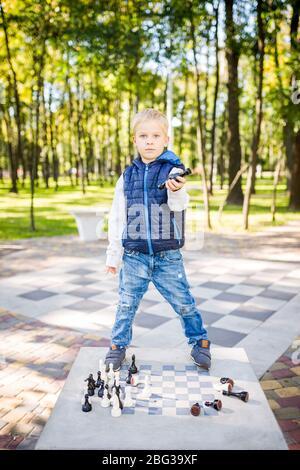 Un drôle de jeune garçon d'origine caucasienne joue sur un lieu d'échecs public dans un parc urbain. Les enfants s'ail et se gâtent au lieu d'étudier. Le sujet de Banque D'Images