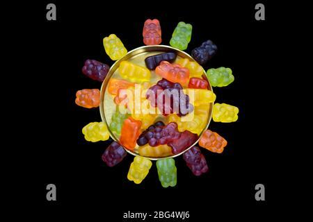 Ours en peluche dans une boîte de bonbons en métal et autour de lui formant le soleil sur un fond noir