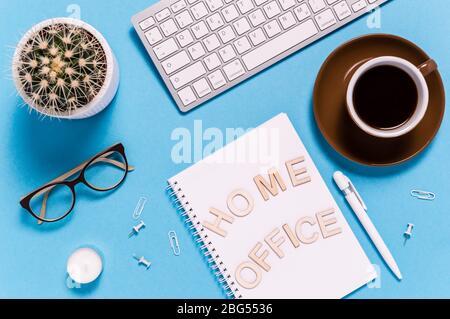 Agencement plat d'un espace de travail moderne avec clavier, tasse à café, bloc-notes, stylo, lunettes et cactus sur fond bleu. Lettres disant Home Office. Vue de dessus