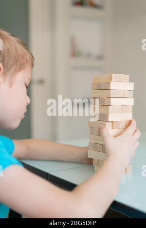 Petit garçon jouant avec jeu de société écologique en bois. Concept. Jeux domestiques en quarantaine. Intérieur