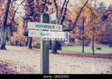 Panneau dans un parc ou une zone boisée avec flèches pointant deux directions opposées vers difficile et facile, concept de différents niveaux de difficulté Banque D'Images