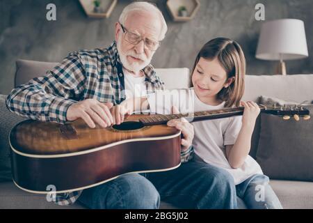 Photo de drôle vieux grand-père petite jolie petite-fille tenant jouer de la guitare enseignant la petite princesse collage passer rester à la maison quarantaine utile Banque D'Images