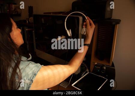 Une femme qui commence à travailler au bureau à domicile en profitant de la lumière du jour prend un casque pour les appels vidéo Banque D'Images