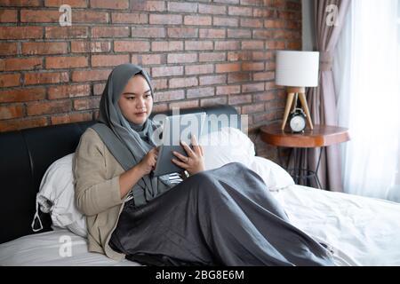 Jeune femme musulmane utilisant un comprimé assis sur le lit à la recherche de calendrier de réservation de billets