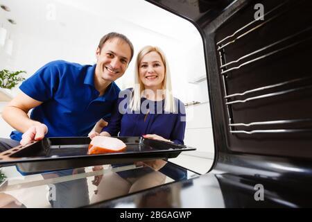 Portrait d'un jeune couple préparant la nourriture dans la cuisine. La jeune femme de ménage tient de la viande fraîchement cuite Banque D'Images
