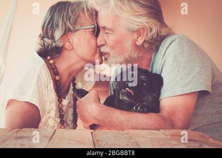 Joyeux vieux couple senior gens dans l'amour embrasser eachOther et câlin leur joli chien noir pug - activité de loisirs à la maison et pour toujours ensemble concept famille A Banque D'Images