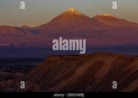 Femme regardant le soleil se coucher sur les Andes montagnes depuis la Vallée de la Lune, le désert d'Atacama, Chili Banque D'Images