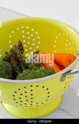 Asperges lavées, brocoli et légumes de carotte dans une passoire verte brillante. Avec fond en bois blanc Banque D'Images