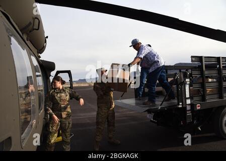 2 e lieutenant, Maram Sweis, officier des opérations médicales de la Garde nationale de l'Arizona et Sgt. Jonathan Atcitty, chef d'équipage de la Garde nationale de l'Arizona et personnel de l'hôpital Kayenta, chargent l'équipement médical de protection personnelle d'un UH-60 Blackhawk dans un camion le 31 mars 2020, à Kayenta, Ariz. la Garde nationale de l'Arizona a volé des EPI médicaux à l'hôpital local en réponse à COVID-19. La Garde de l'Arizona a réagi au pays dans des situations d'urgence comme la sécurité de l'aéroport après le 11 septembre 2011, le Monument Fire en 2011, l'ouragan Harvey en 2017 et les inondations de Havasupai en 2018 (États-Unis Photo de la Garde nationale aérienne par Tech. SG