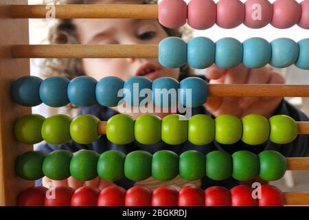 Jeune fille (03 ans) comptant sur Abacus. Concept d'apprentissage. Des gens réels. Espace de copie