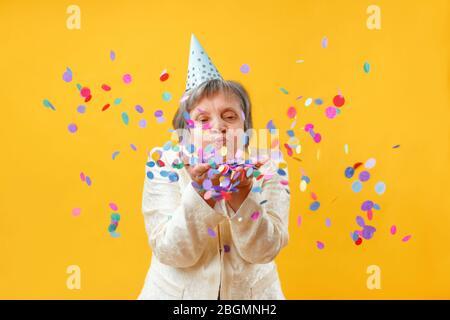 Portrait d'une femme âgée en studio sur fond jaune. Une dame gaie soufflant sur des confettis. Concept de fête. Banque D'Images