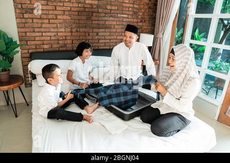 la famille asiatique prépare des vêtements et met en valise pour transporter quand mudik aller à la maison de village arrière Banque D'Images