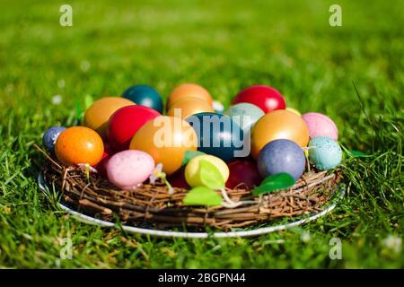 Stock photo des oeufs de Pâques dans un panier en bois sur l'herbe verte comme symbole de Pâques dans la religion chrétienne.