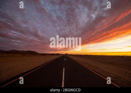 La route pavée de Sesriem à Sossusvlei dans le parc national du Namib-Naukluft en Namibie juste avant le coucher du soleil.
