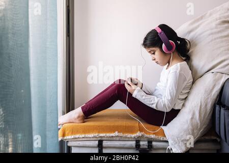 petite fille assise devant sa fenêtre avec casque regardant des vidéos sur le téléphone, divertissement à la maison pour enfants concept Banque D'Images
