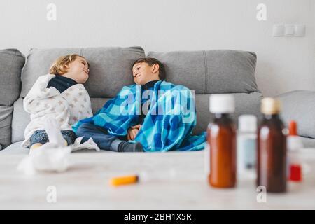 Les frères et sœurs malades assis sur le canapé à la maison avec des médicaments sur le plan d'examen au premier plan