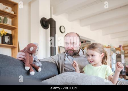 Père et petite fille assis ensemble sur le canapé à la maison jouant avec des jouets