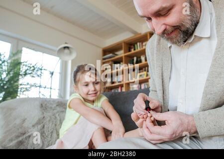 Père peignant les ongles de sa fille avec vernis à ongles rouge sur le canapé dans le salon Banque D'Images