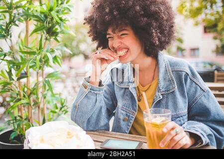 Bonne jeune femme avec des frites de coiffo afro dans un café en plein air de la ville