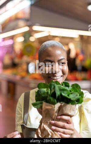 Portrait d'une femme heureuse tenant un sac en papier dans un hall de marché Banque D'Images