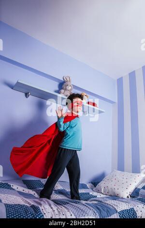 Petit garçon jouant super héros, debout sur son lit