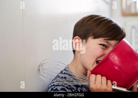 Portrait d'un garçon avec bol mélangeur rouge et batteur à œufs dans la cuisine Banque D'Images