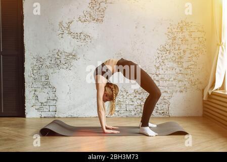 Une jeune fille charmante va pour le sport à la maison dans un uniforme de sport sur un tapis. Sport, belle jeune femme pratiquant le yoga, faisant la pose de pont, debout à Urdhva Dhanurasana, s'entraîner à porter des vêtements de sport