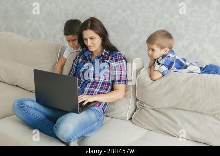 Restez à la maison, maman et ses enfants regardant une vidéo conférence sur un ordinateur portable. Télétravail le concept de distance sociale. Quarantaine, heure de la famille. Fermer Banque D'Images