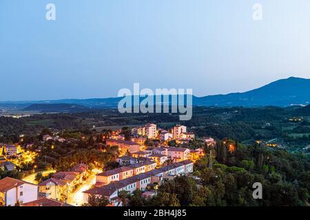 Village de Chiusi la nuit en Toscane, Italie avec lumières illuminées sur les rues et maisons sur le toit sur la campagne de montagne et les collines vallonnées Banque D'Images