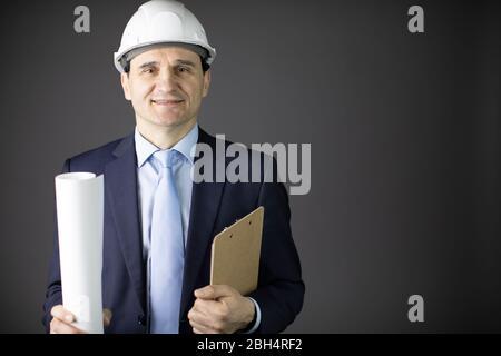 un constructeur positif dans un casque des vêtements formels peut dessiner en souriant
