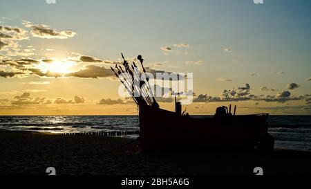 Bateau de pêche au coucher du soleil sur la plage de la mer Baltique près de Rewal en Pologne Banque D'Images