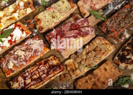 Assortiment de tranches de pizza rustiques maison rectangulaires sur table en bois. Banque D'Images