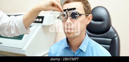 médecin ophtalmologiste en laboratoire d'opticiens d'examen avec patient mâle. Oeil d'homme