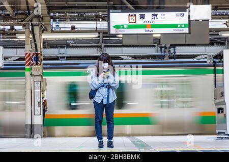 Japon, Honshu, Tokyo, Tokyo Station, plate-forme Yamanote Line, Jeune Femme avec masque en attente de train Banque D'Images
